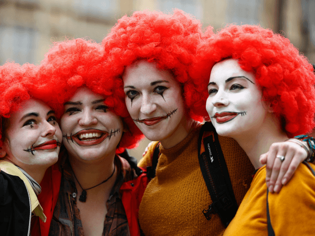 Demonstrators dressed as Ronald McDonald, the mascot of US burger chain McDonalds, pose for a photograph as they participate in a protest over working conditions and the use of zero-hour contracts at British outlets of US burger chain, in central London on September 4, 2017. McDonald's staff have gone on …