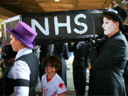 MANCHESTER, ENGLAND - OCTOBER 04: People carry a mock-up of a coffin with the letters 'NHS' on the side as they take part in an anti-austerity protest during the first day of the Conservative Party Autumn Conference 2015 on October 4, 2015 in Manchester, England. Conservative Party members are in …