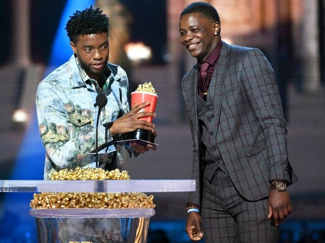 Actor Chadwick Boseman (L), winner of the Best Hero award for 'Black Panther,' presents his trophy to James Shaw Jr. onstage during the 2018 MTV Movie And TV Awards at Barker Hangar on June 16, 2018 in Santa Monica, California. (Photo by Kevin Winter/Getty Images for MTV)