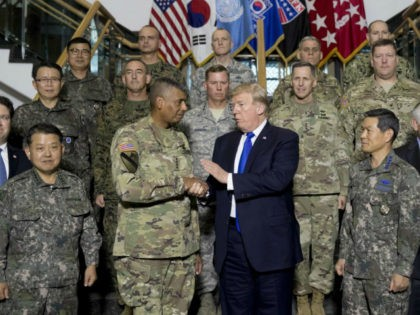 U.S. President Donald Trump, center, accompanied by United States Forces Korea Commander Gen. Vincent Brooks, center left, and Secretary of State Rex Tillerson, second right, poses for a group photo at the Eighth Army Operational Command Center at Camp Humphreys in Pyeongtaek, South Korea, Tuesday, Nov. 7, 2017. Trump is …