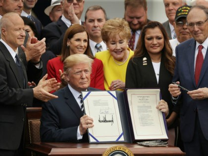 U.S. President Donald Trump holds up the Veterans Affairs Mission Act he signed during a ceremony with members of Congress, including House Veterans Affairs Committee Chairman Phil Roe (R-TN) (R), and veterans in the Rose Garden at the White House on June 6, 2018 in Washington, DC. The new law …