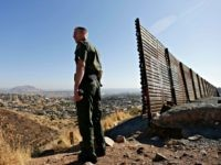 In this June 13, 2013 file photo, US Border Patrol agent Jerry Conlin looks out over Tijuana, Mexico, by the old border wall along the US - Mexico border, where it ends at the base of a hill in San Diego. U.S. Customs and Border Protection has begun testing body-worn …