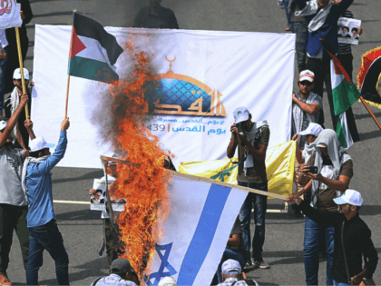 "Iraqi Popular Mobilization Forces burn a representation of Israeli flag as they hold a Palestinian flag during ""al-Quds"" Day, Arabic for Jerusalem, in Baghdad, Iraq, Friday, June 8, 2018. Jerusalem Day began after the 1979 Islamic Revolution in Iran, when the Ayatollah Khomeini declared the last Friday of the Muslim …"