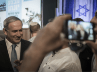 Israeli Prime Minister Benjamin Netanyahu talks with a visitor at the opening of an exhibition showcasing the 1976 Israeli commando rescue raid that freed hostages from a hijacked plane at Entebbe, Uganda, as he attends the event at the Yitzhak Rabin Center in Tel Aviv, Israel, Thursday, July 9, 2015. …