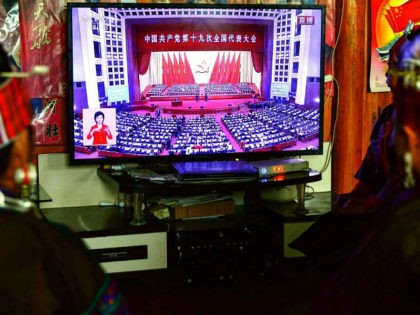 This photo taken on October 18, 2017 shows people of the Miao ethnic minority watching the opening session of the 19th Communist Party Congress on a television in Jianhe in China's southwestern Guizhou province. President Xi Jinping declared China is entering a 'new era' of challenges and opportunities on October …