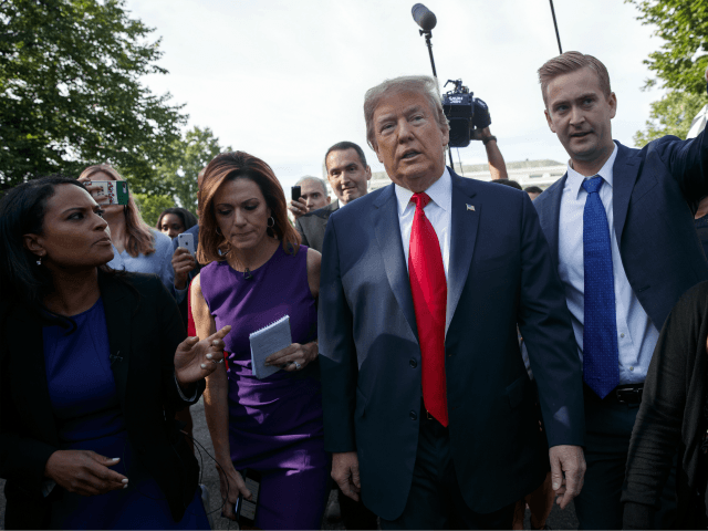 President Donald Trump walks to an interview on the North Lawn of the White House Friday