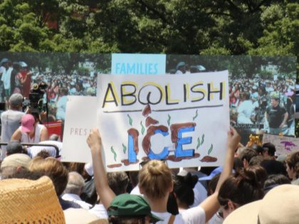 "A sign with the words ""Abolish ICE"" depicting someone's rear end defecating on the word ""ICE"" in an apparent insult to the immigration enforcement agency. (Credit: Michelle Moons/Breitbart News)"