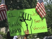 An open borders protester holding a sign depicting a raised fist flanked by two U.S. flags. (Credit: Matt Perdie/Breitbart News)