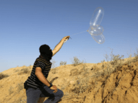 A masked Palestinian launches a Balloon loaded with flammable materials to be flown toward Israel, at the Israel-Gaza border, in Rafah in the southern Gaza Strip on June 17, 2018. (Photo by SAID KHATIB / AFP) (Photo credit should read SAID KHATIB/AFP/Getty Images)