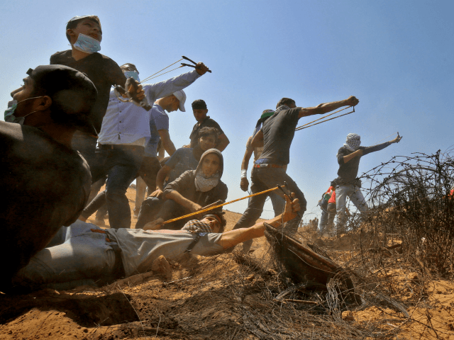 Hamas Palestinian protesters use slingshots to hurl stones toward Israeli forces during clashes near the border with Israel, east of Khan Yunis in the southern Gaza Strip on June 8, 2018. (Photo by SAID KHATIB / AFP) (Photo credit should read SAID KHATIB/AFP/Getty Images)