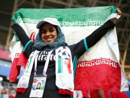 A female Iranian fan holds up her country's flag as she waits for the start of the group B match between Iran and Portugal at the 2018 soccer World Cup at the Mordovia Arena in Saransk, Russia, Monday, June 25, 2018. (AP Photo/Francisco Seco)