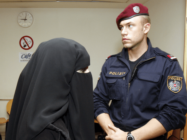 Mona S., left, wife of terror suspect Mohamed M., unseen, is accompanied by a police man as she enters the court room prior to the start of the Austrian terror trial at court in Vienna, Austria, on Thursday, Nov. 13, 2008. The Muslim couple convicted of making online terrorism threats …