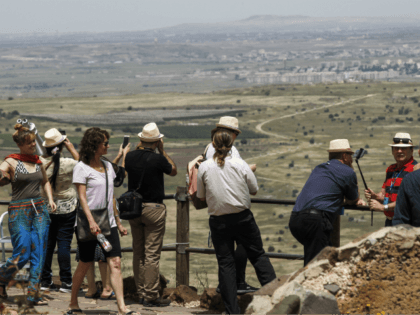 Tourists visit an Israeli army post on Mount Bental in the Israeli-annexed Golan Heights on May 10, 2018. - Israel's army said today it had carried out widespread raids against Iranian targets in Syria overnight after rocket fire towards its forces it blamed on Iran, marking a sharp escalation between …