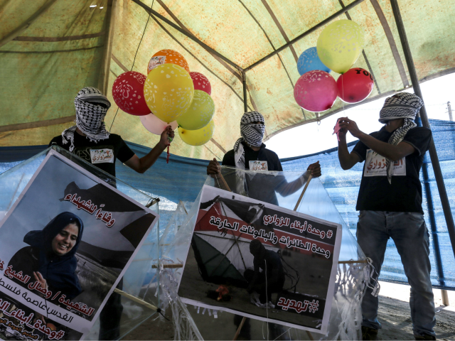 Palestinian protesters holds ballons and kites before loading them with flammable material to be flown towards Israel, at the Israel-Gaza border in al-Bureij, central Gaza Strip on June 14, 2018. (Photo by MAHMUD HAMS / AFP) (Photo credit should read MAHMUD HAMS/AFP/Getty Images)