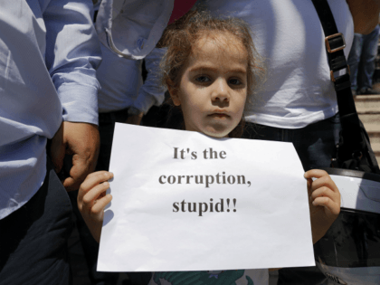 A Jordanian child holds a sign during an anti-austerity rally, on June 6, 2018 in Amman. - Jordanian unions staged a nationwide strike today over IMF-backed austerity measures including a proposed income tax law that has sparked a week of angry demonstrations. (Photo by AHMAD GHARABLI / AFP) (Photo credit …