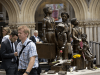 "Flowers lie in memory of Britain's Sir Nicholas Winton on German-born Jewish sculptor Frank Meisler's ""Kindertransport"" (German for children transport) memorial statue outside Liverpool Street Station in London, Thursday, July 2, 2015. Winton, a humanitarian who almost single-handedly saved more than 650 Jewish children from the Holocaust, earning himself the …"