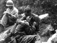 An American soldier comforts a fellow infantryman whose close friend has been killed in action, Haktong-ni area, Korea, August 1950. A corpsman fills out casualty tags in the background. US Army photo. (Photo by Interim Archives/Getty Images)