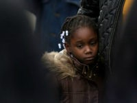 A girl stands with her mother near the spot where a youth was shot and killed by a policeman November 13, 2007 in Brooklyn, New York. After receiving a 911 call from the youth?s mother, New York City police shot and killed an 18-year-old youth who was armed with a …