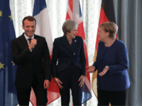 French President Emmanuel Macron, British Prime Minister Theresa May and German Chancellor Angela Merkel share a joke as they arrive for the start of an EU-Western Balkans Summit in Sofia on May 17, 2018. - European Union leaders will meet their Balkan counterparts to hold out the promise of closer …