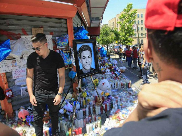 """Celebrity artist Samil Alva, left, steps over candles after placing a portrait he painted of 15-year-old Lesandro Guzman-Feliz at a community memorial in New York on Tuesday June 26, 2018. The teenager was killed at the bodega last Wednesday in a machete attack. """"I want my painting to bring love, …"""