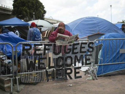 A migrant at reads a news paper at a migrant camp at the El Chaparral Border Crossing, in Tijuana, Mexico, Wednesday, May 2, 2018. Tension between the Mexican government and Central American asylum seekers simmered Wednesday as men, women and children camped in a large plaza for a fourth straight …