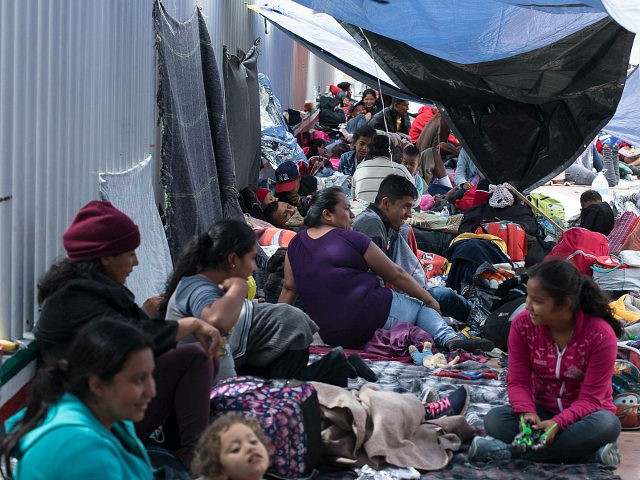 People who traveled with the annual caravan of Central American migrants, rest where the group set up camp to wait for access to request asylum in the US, outside the El Chaparral port of entry building at the US-Mexico border in Tijuana, Mexico, Monday, April 30, 2018. About 200 people …