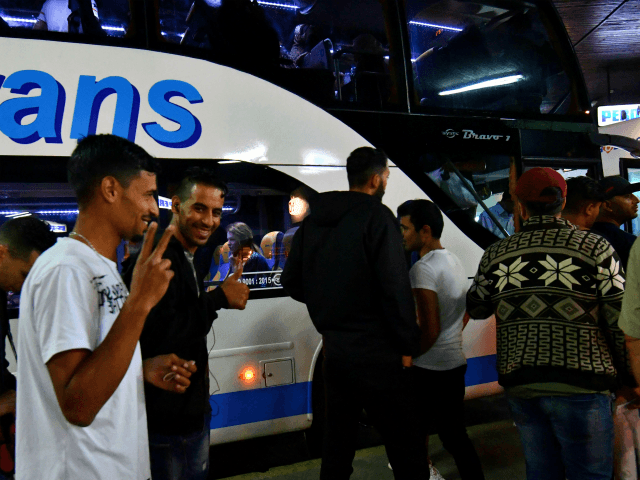 Migrants board a night bus, on their way to North-Western Bosnian town of Bihac, late on June 7, 2018 at Sarajevo bus station. - African-Asian migrants make their stop in Bihac, where they rest before continuing 'the final Bosnian leg' on their journey towards Velika Kladusa, Bosnian town, on Bosnia …