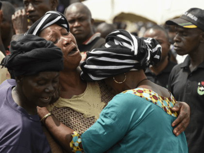 A woman cries while trying to console a woman who lost her husband during the funeral service for people killed during clashes between cattle herders and farmers, on January 11, 2018, in Ibrahim Babangida Square in the Benue state capital Makurdi. Violence between the mainly Muslim Fulani herdsmen and Christian …