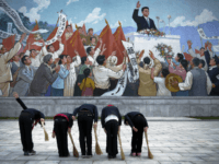 FILE - School girls holding brooms bow to pay their respects toward a mural that depicts the late North Korean leader Kim Il Sung delivering a speech, before sweeping the area surrounding the mural on Dec. 1, 2015, in Pyongyang, North Korea. (AP Photo/Wong Maye-E, File)