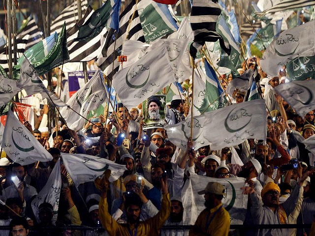 Supporters of Muttahida Majlis-e-Amal (MMA), a religious parties alliance waves flags during a public meeting in Lahore on May 13, 2018, in the connection of upcoming election. - Six mainstream religious parties of Pakistan had decided to restore Muttahida Majlis-e-Amal (MMA), ten years after the political alliance was dissolved over …