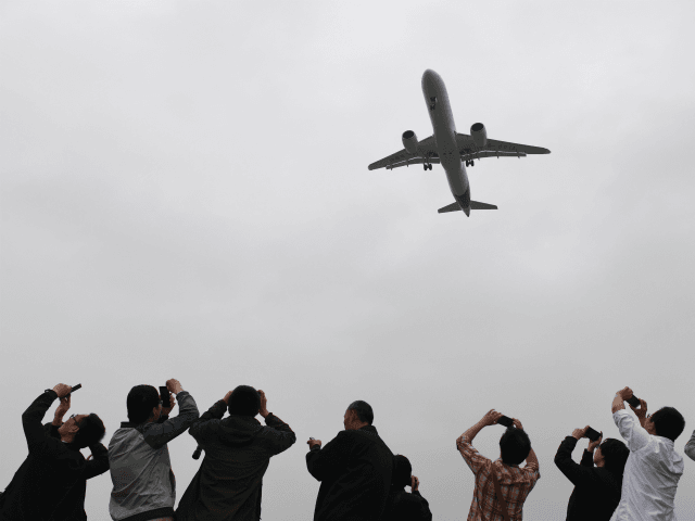 Spectators take photos as they watch the Comac C919, China's first large passenger jet, coming in for a landing on its maiden flight at Shanghai's Pudong airport on May 5, 2017. The first large made-in-China passenger plane took off on its maiden test flight on May 5, marking a key …
