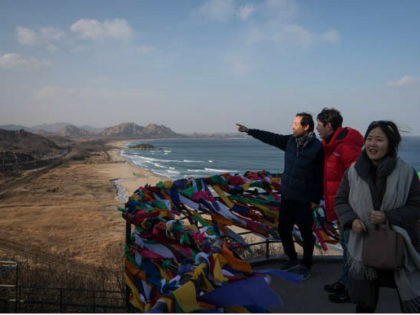 In a photo taken on February 11, 2018, a family pose for photos at an observation deck overlooking the Demilitarized Zone (DMZ) and coastline of North Korea, at the Goseong Unification Observatory on South Korea's northeast coast. Despite the sudden thaw in ties with diplomatic visits during the Pyeongchang 2018 …