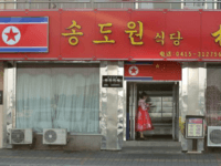 A North Korean woman and hostess stands outside Song Do Won in 2015. The restaurant recently closed, according to a source who spoke to Yonhap. File Photo by Stephen Shaver/UPI