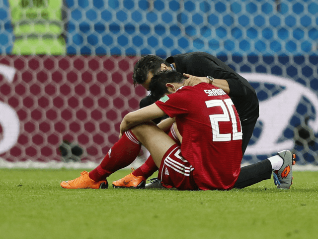 Iran's Sardar Azmoun is consoled at the end of the group B match between Iran and Spain at the 2018 soccer World Cup in the Kazan Arena in Kazan, Russia, Wednesday, June 20, 2018. Spain won 1-0. (AP Photo/Frank Augstein)
