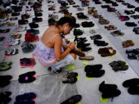 A woman places one of the hundreds of shoes in memory of those killed by Hurricane Maria in front of the Puerto Rico Capitol, in San Juan, Friday, June 1, 2018. Puerto Rico's Institute of Statistics announced that it has sued the U.S. territory's health department and demographic registry seeking …