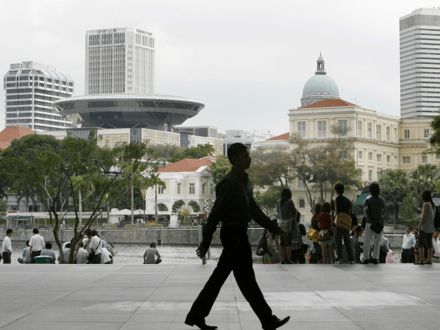 An office worker is silhouetted against the financial district while tourists sit by the waterfront, Friday, Feb. 19, 2010 in Singapore. Singapore raised its 2010 GDP forecast and now expects the city-state's economy to grow as much as 6.5 percent after contracting last year. (AP Photo/Wong Maye-E)