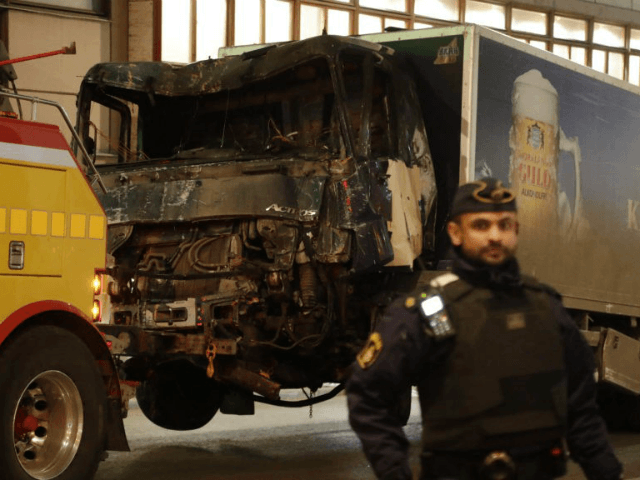 A destroyed truck is pull away by a service car after it was driven into a department store in Stockholm, Sweden, Saturday, April 8, 2017. The hijacked beer truck plowed into pedestrians at the central Stockholm department store on Friday, sending screaming shoppers fleeing in panic in what Sweden's prime …