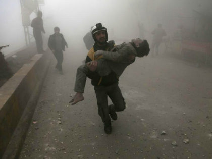 TOPSHOT - EDITORS NOTE: Graphic content / A volunteer from the Syrian Civil Defence (known as the White Helmets) carries a wounded boy after digging him out of the rubble following an air strike on Hamouria, in the besieged rebel-held Eastern Ghouta area near Damascus, on January 9, 2018. Air …