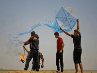 Palestinian protestors prepare to fly a kite loaded with an incendiary during a demonstration along the border with Israel east of Jabalia in the central Gaza Strip on June 8, 2018. - Palestinians in the besieged coastal enclave have used kites carrying burning cans to set ablaze Israeli fields, torching …