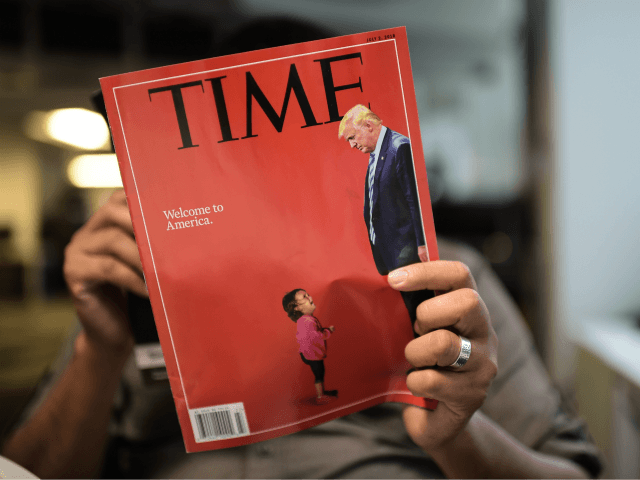 An AFP journalists reads a copy of Time Magazine with a front cover using a combination of pictures showing a crying child taken at the US Border Mexico and a picture of US President Donald Trump looking down, on June 22, 2018 in Washington DC. (Photo by Eric BARADAT / …
