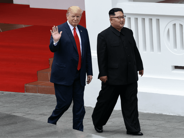 North Korea's leader Kim Jong Un (R) walks with US President Donald Trump (L) after lunch and during a break in talks at their historic US-North Korea summit, at the Capella Hotel on Sentosa island in Singapore on June 12, 2018. - Donald Trump and Kim Jong Un became on …
