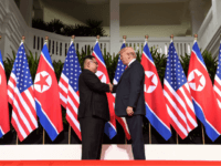 North Korea's leader Kim Jong Un (L) shakes hands with US President Donald Trump (R) at the start of their historic US-North Korea summit, at the Capella Hotel on Sentosa island in Singapore on June 12, 2018. - Donald Trump and Kim Jong Un have become on June 12 the …