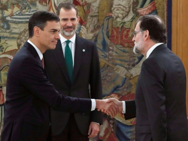 Spain's new Prime Minister Pedro Sanchez (l) shakes hands with predecessor Mariano Rajoy in front of Spain's King Felipe VI during the swearing-in ceremony