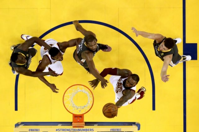 LeBron James of the Cleveland Cavaliers attempts a layup against Kevin Durant and Klay Thompson of the Golden State Warriors in Game 2 of the 2018 NBA Finals at ORACLE Arena on June 3, 2018 in Oakland, California
