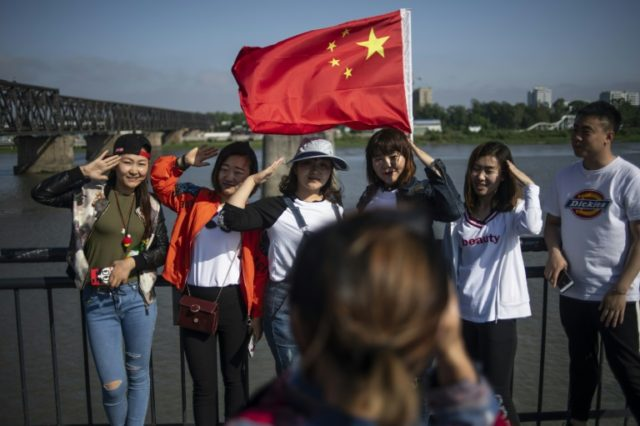 Chinese tourists take pictures on Dandong's Broken Bridge, which links China with North Korea over the Yalu River
