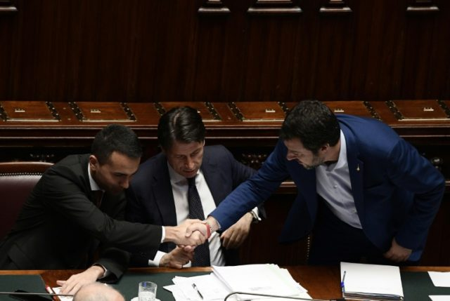 Italy's incoming premier Giuseppe Conte (C) shakes hands with far-right leader Matteo Salvini (L) and Five Star Movement head Luigi Di Maio after Tuesday's successful senate vote