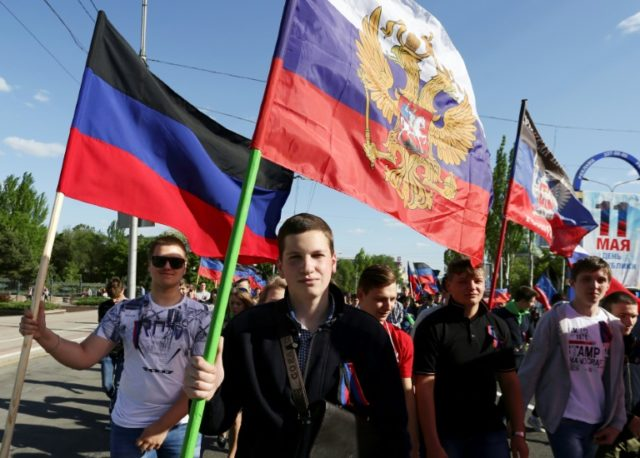 People march on May 11, 2018, with Russian flags and flags of the Donetsk People's Republic on the fourth anniversary of the self-proclaimed republic, in the region where pro-Russian separatists and Ukraine are in conflict