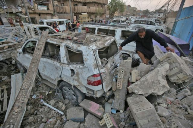 Iraqis inspect the aftermath of an explosion in Baghdad's Sadr City district, on June 7, 2018