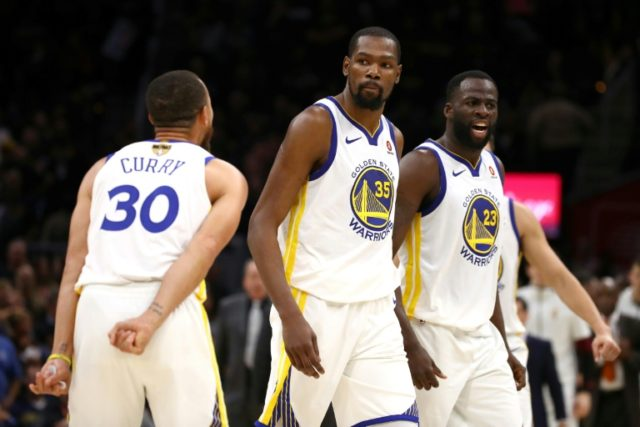 Stephen Curry (L), Draymond Green (R) and Kevin Durant of the Golden State Warriors celebrate after scoring against the Cleveland Cavaliers in the second half during Game Three of the 2018 NBA Finals, in Cleveland, Ohio, on June 6