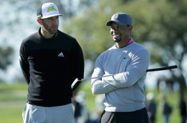 Dustin Johnson and Tiger Woods wait to putt on the 12th green during the second round of the Farmers Insurance Open at Torrey Pines North on January 27, 2017 in San Diego, California
